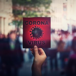 Hand holds red banner warning rapidly spreading Coronavirus on crowded city streets. Deadly Corona virus epidemic outbreak, unknown influenza, fever or flu symptoms infecting people. Pandemic risk.