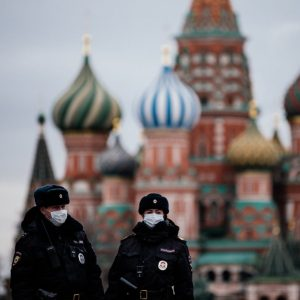"TOPSHOT – Russian police officers patrol on March 30, 2020 on the deserted Red square in front of Saint Basil's Cathedral in Moscow as the city and its surrounding regions imposed lockdowns today, that were being followed by other Russian regions in a bid to slow the spread of the COVID-19 infection caused by the novel coronavirus. – The enforcement of the strict new rules, which Moscow Mayor suddenly announced for the capital late Sunday, coincide with the beginning of a ""non-working"" week declared by Russian President the week before. (Photo by Dimitar DILKOFF / AFP) (Photo by DIMITAR DILKOFF/AFP via Getty Images)"