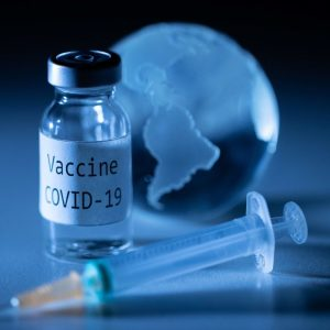 <p>An illustration picture taken on November 19, 2020, shows a vial with Covid-19 Vaccine sticker, a syringe and an earth globe. (Photo by JOEL SAGET / AFP)</p>